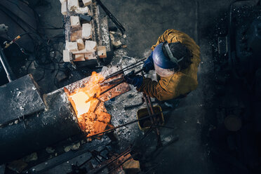 Overhead view of blacksmith shaping red hot metal rod in workshop furnace - CUF11075