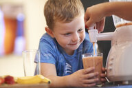 Mother pouring fruit smoothie for son in kitchen - CUF11186
