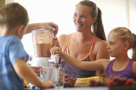 Mature woman and children blending fresh smoothie in kitchen - CUF11189