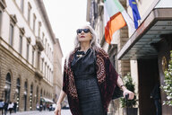 Mature woman with long grey hair with wheeled suitcase outside hotel in Florence, Italy - CUF11276
