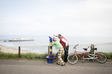 Quirky couple using tower viewer, Bournemouth, England - CUF11291