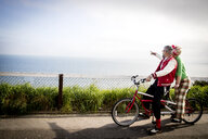 Quirky couple sightseeing on tandem bicycle, Bournemouth, England - CUF11294