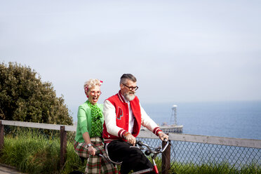 Quirky couple sightseeing on tandem bicycle, Bournemouth, England - CUF11300