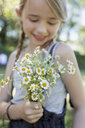 Girl pleased with bunch of camomile flowers - CUF11339