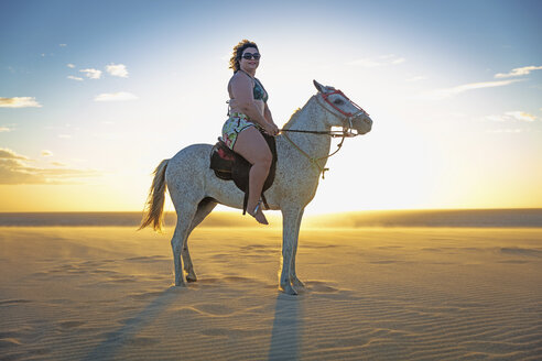 Woman riding horse on beach, side view, Jericoacoara, Ceara, Brazil, South America - CUF11351