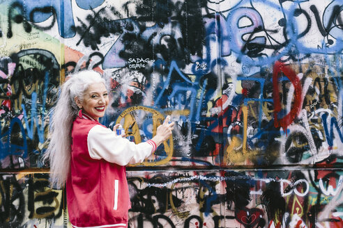 Portrait of mature woman in baseball jacket spray painting graffiti wall - CUF11375