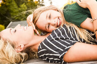 Mother and daughter lying on wooden decking outdoors - CUF11393