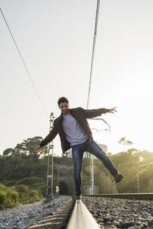 Young man standing on railroad track - AFVF00478