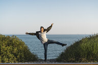 Spain, young man jumping in the air at the beach - AFVF00481
