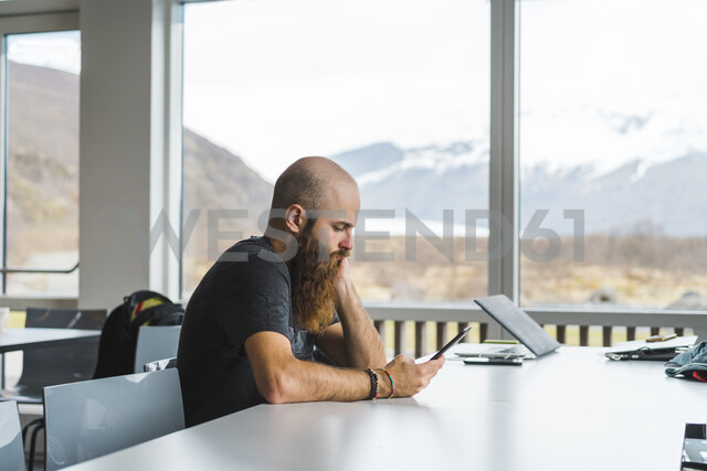 Island, pensive Hipster sitting in a coffee shop looking at cell phone - AFVF00484