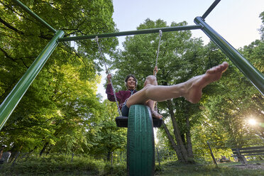 Smiling young woman on a swing listening music with headphones - BEF00089