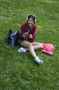Young woman with headphones sitting on a meadow using cell phone - BEF00092