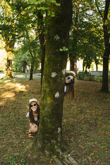 Portrait of two young female friends in trilby hats behind park tree - CUF11562