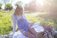 Young woman reading book on picnic blanket in field, Majorca, Spain - CUF11807