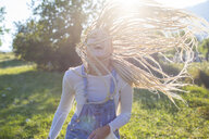 Fun young woman with long plaited blond hair in field, Majorca, Spain - CUF11810