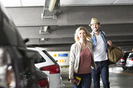Young couple walking through airport carpark - CUF11825