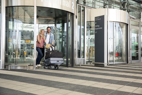 Happy young couple with luggage trolley leaving airport terminal - CUF11828