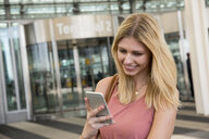 Young woman looking at smartphone outside airport terminal - CUF11834