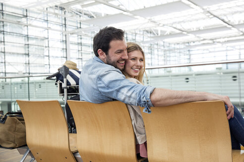 Young couple waiting on seats in airport departure lounge - CUF11843