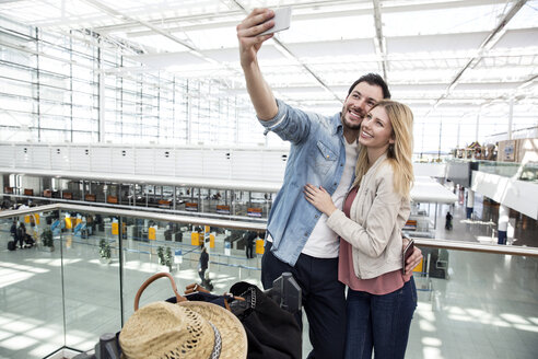 Young couple taking smartphone selfie in airport terminal - CUF11846