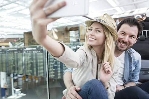 Young couple taking smartphone selfie in airport terminal - CUF11849