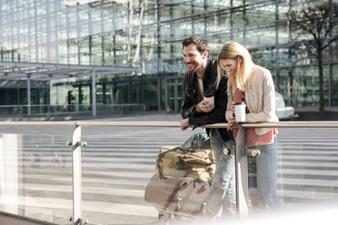 Young couple with coffee and baggage trolley outside airport - CUF11852
