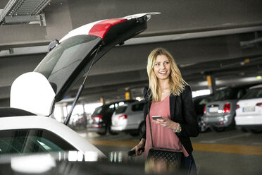 Young woman waiting at open car boot with smartphone in airport carpark - CUF11855