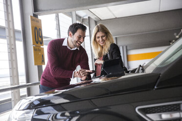 Young couple looking at digital tablet in airport carpark - CUF11858