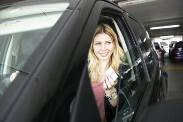 Young woman holding parking ticket in airport carpark - CUF11861