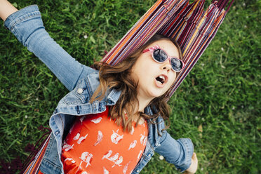Portrait of singing girl wearing sunglasses lying in hammock - ANHF00047