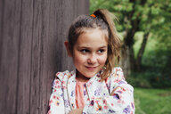 Portrait of smiling girl leaning against wooden wall - ANHF00056