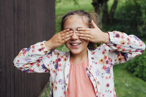 Portrait of smiling girl covering eyes with her hands - ANHF00059