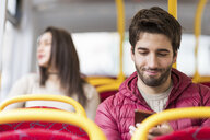 UK, London, portrait of smiling young man using cell phone in bus - WPEF00265