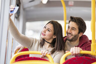 UK, London, portrait of smiling young couple taking selfie with smartphone in bus - WPEF00268