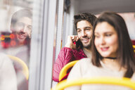 UK, London, portrait of smiling young man on the phone in a bus - WPEF00271