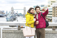 UK, London, young couple with coffee to go standing on bridge over the Thames taking selfie with smartphone - WPEF00283