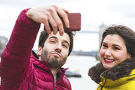 UK, London, Portrait of young couple  taking selfie with smartphone - WPEF00286