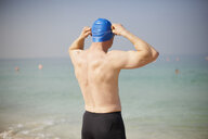 Rear view of mature man adjusting swimming cap on beach, Dubai, United Arab Emirates - CUF11873