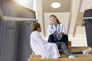 Two female doctors taking a break on hospital stairway chatting - CUF11999