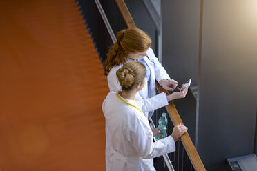 High angle view of two female doctors on hospital balcony looking at smartphone - CUF12002