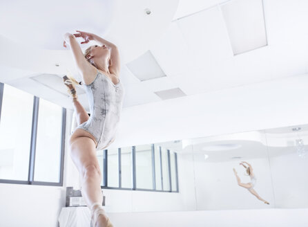 Young female ballet dancer leaping in dance studio - CUF12011