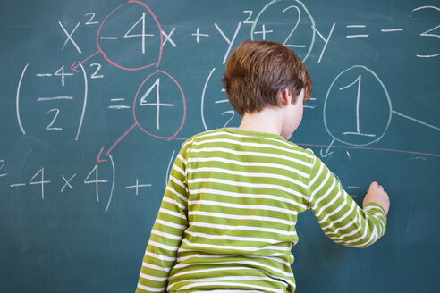 Rear view of primary schoolboy answering equation on classroom blackboard - CUF12014