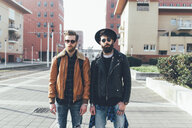 Portrait of two young male hipster friends standing in city housing estate - CUF12026