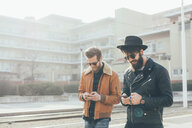 Two young male hipsters looking at smartphones  at city tram station - CUF12032