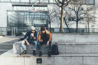Two young male hipsters sitting on wall looking at smartphone - CUF12038