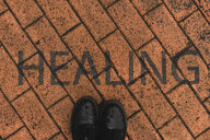 Black shoes on orange pavement with stenciled word 'Healing' - AFVF00491