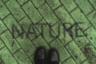 Black shoes on green pavement with stenciled word 'Nature' - AFVF00494