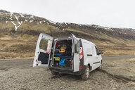 Iceland, man lying in van playing guitar - AFVF00503