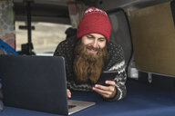 Portrait of smiling hipster lying in van using smartphone and laptop - AFVF00506