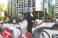 Red haired businesswoman pushing hire bicycle outside city office - CUF12064